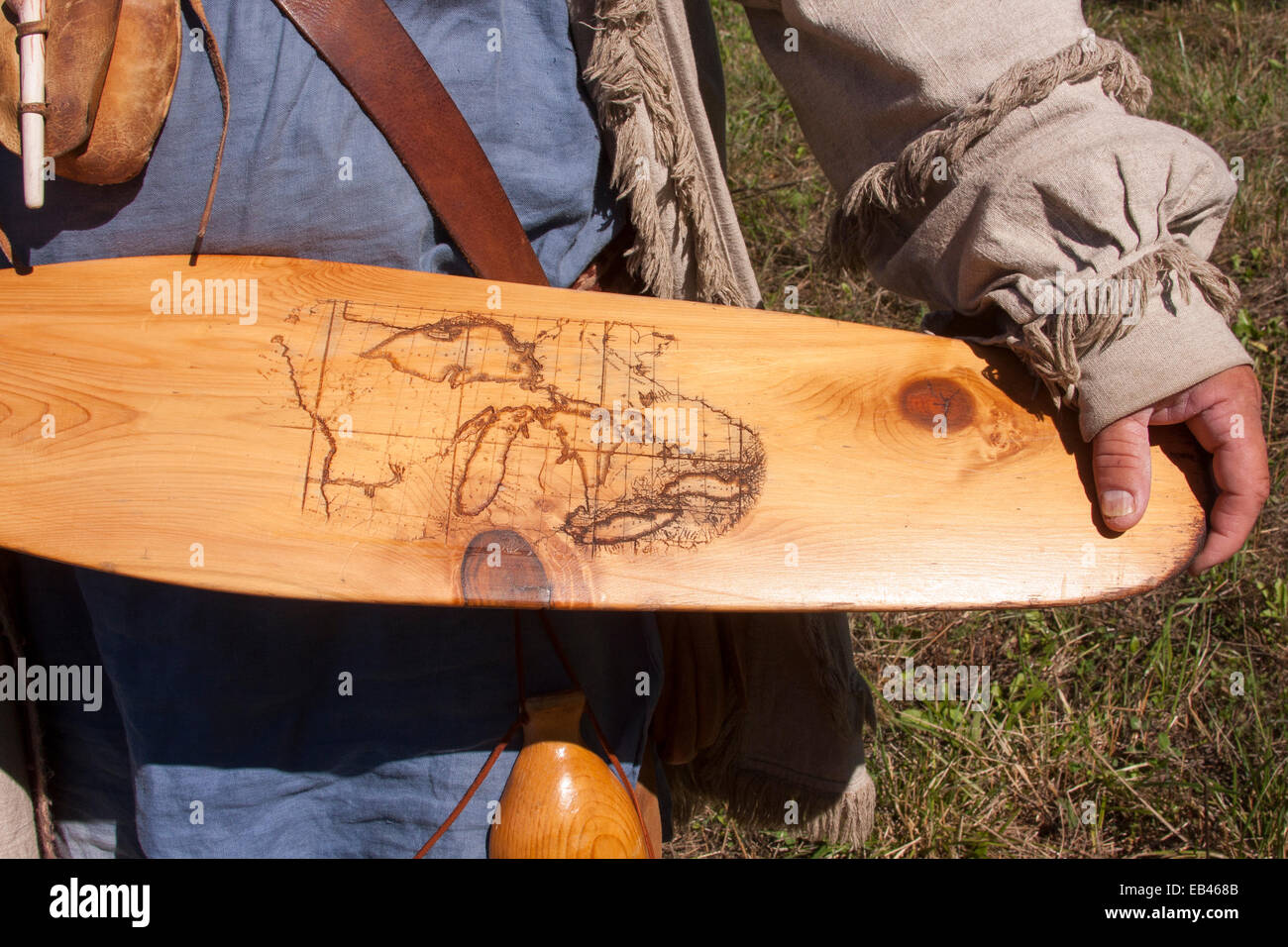 French Voyageur Explorer holding a canoe paddle with an old map of the Great Lakes burned onto it - Stock Image