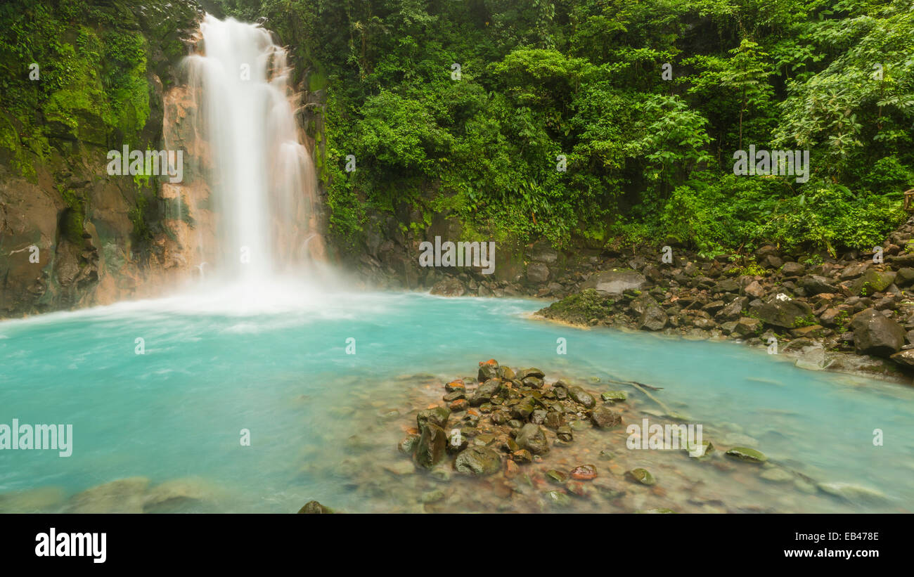 Panoramic image of the cerulean blue waters of the Rio Celeste Waterfall in Volcan Tenorio National Park, Costa - Stock Image