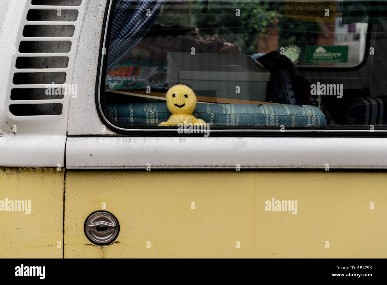 Yellow in yellow: the smiling face of a child's cuddly toy looking out the window of a VW camper van - Stock Image
