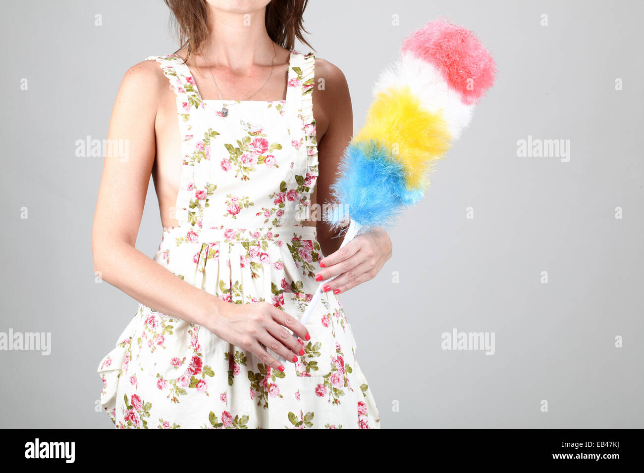 Housewife cleaning the house with feather duster. Model released - Stock Image