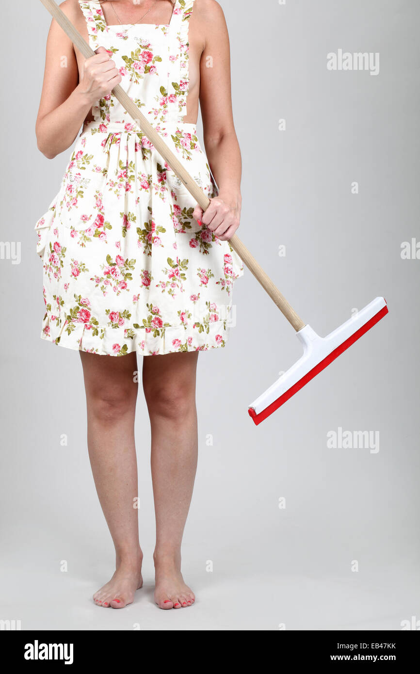 Housewife cleaning the house with a mop. Model released - Stock Image