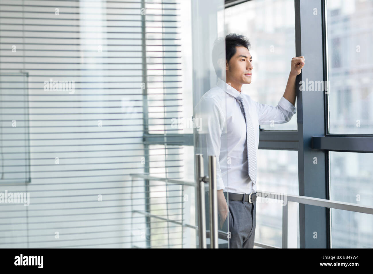 Young businessman looking through window - Stock Image