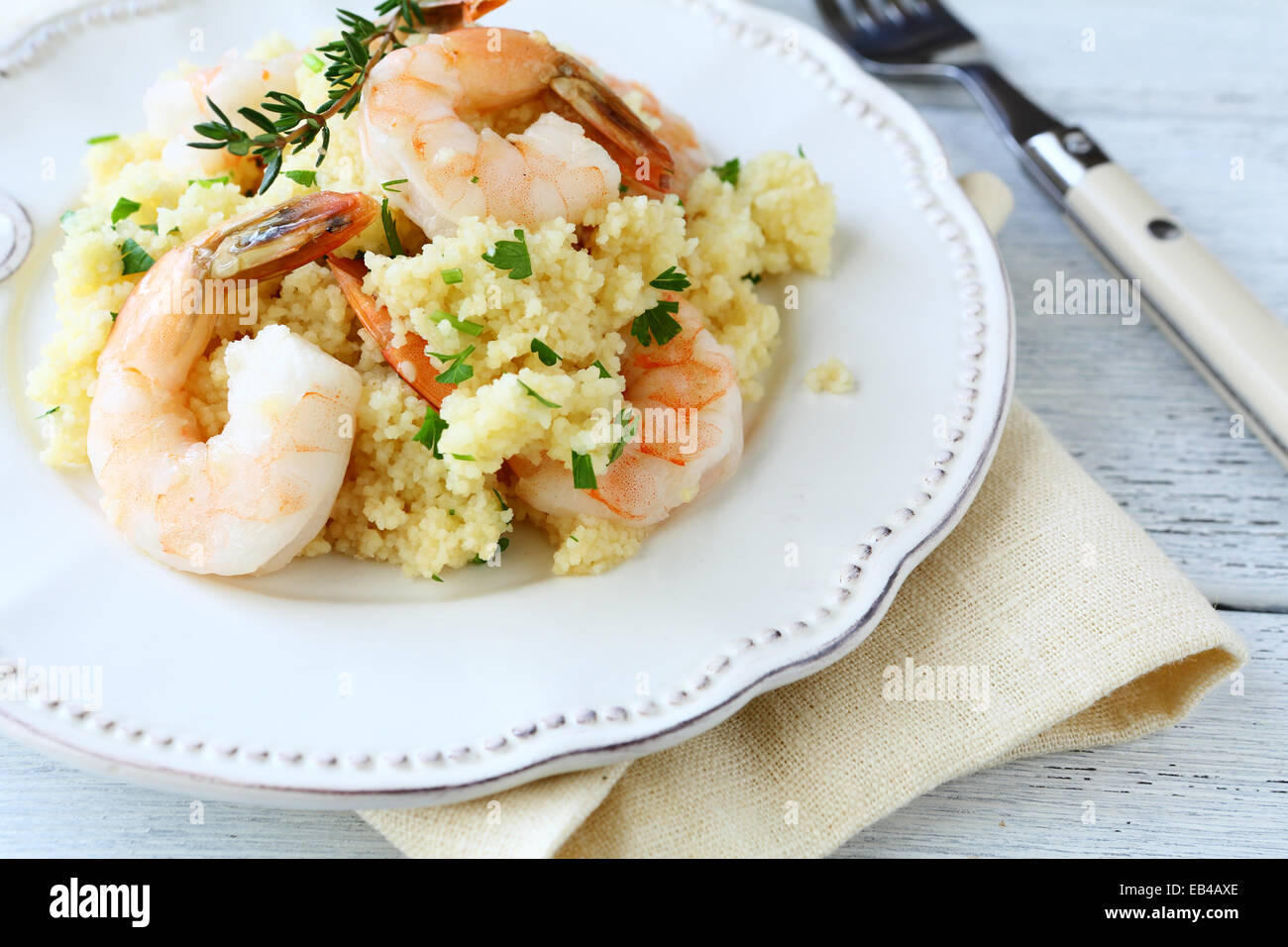 Delicious couscous with shrimp and parsley on the plate, food closeup - Stock Image