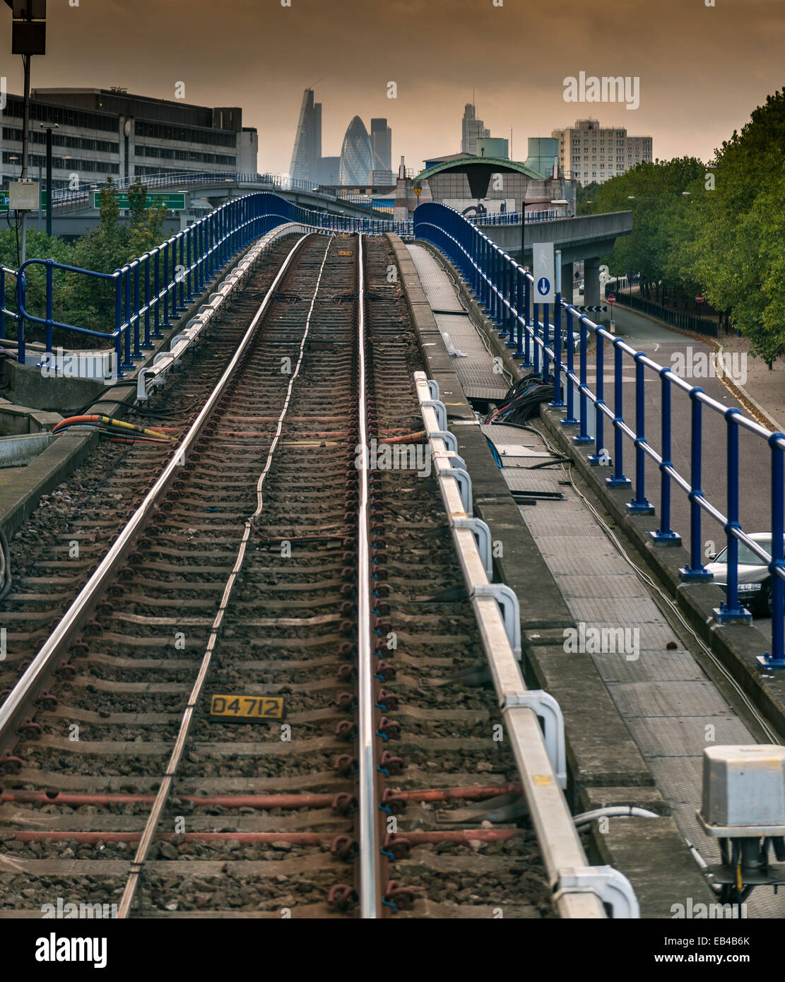 Docklands Light Railway connecting Canary Wharf and the City of London with City skyscrapers in the background - Stock Image