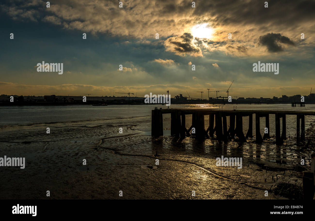Tide out: sunset on the mud banks of the River Thames looking towards Greenwich - Stock Image