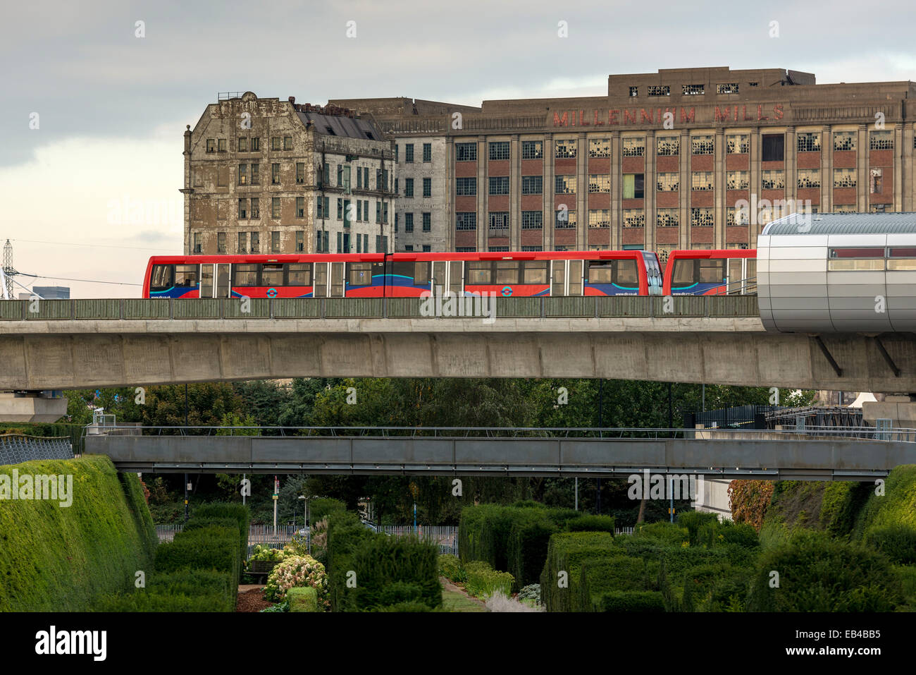 A Docklands Light Railway train passing derelict Docklands warehouse, Millennium Mills in East London - Stock Image