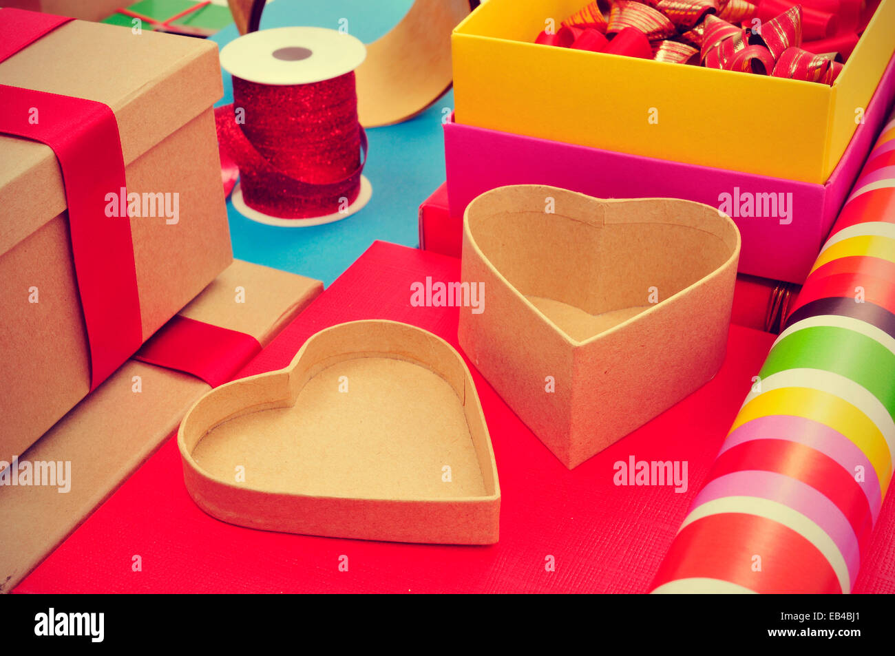a pile of different boxes, wrapping paper, ribbon and ribbon bows of different colors to prepare gifts - Stock Image