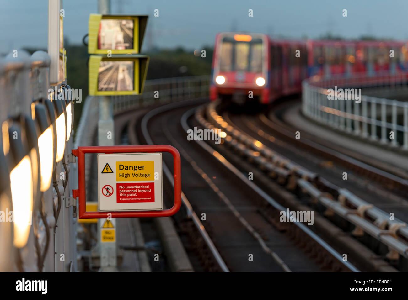 Electricity warning: Danger High Voltage sign on Docklands Light Railway platform in East London - Stock Image