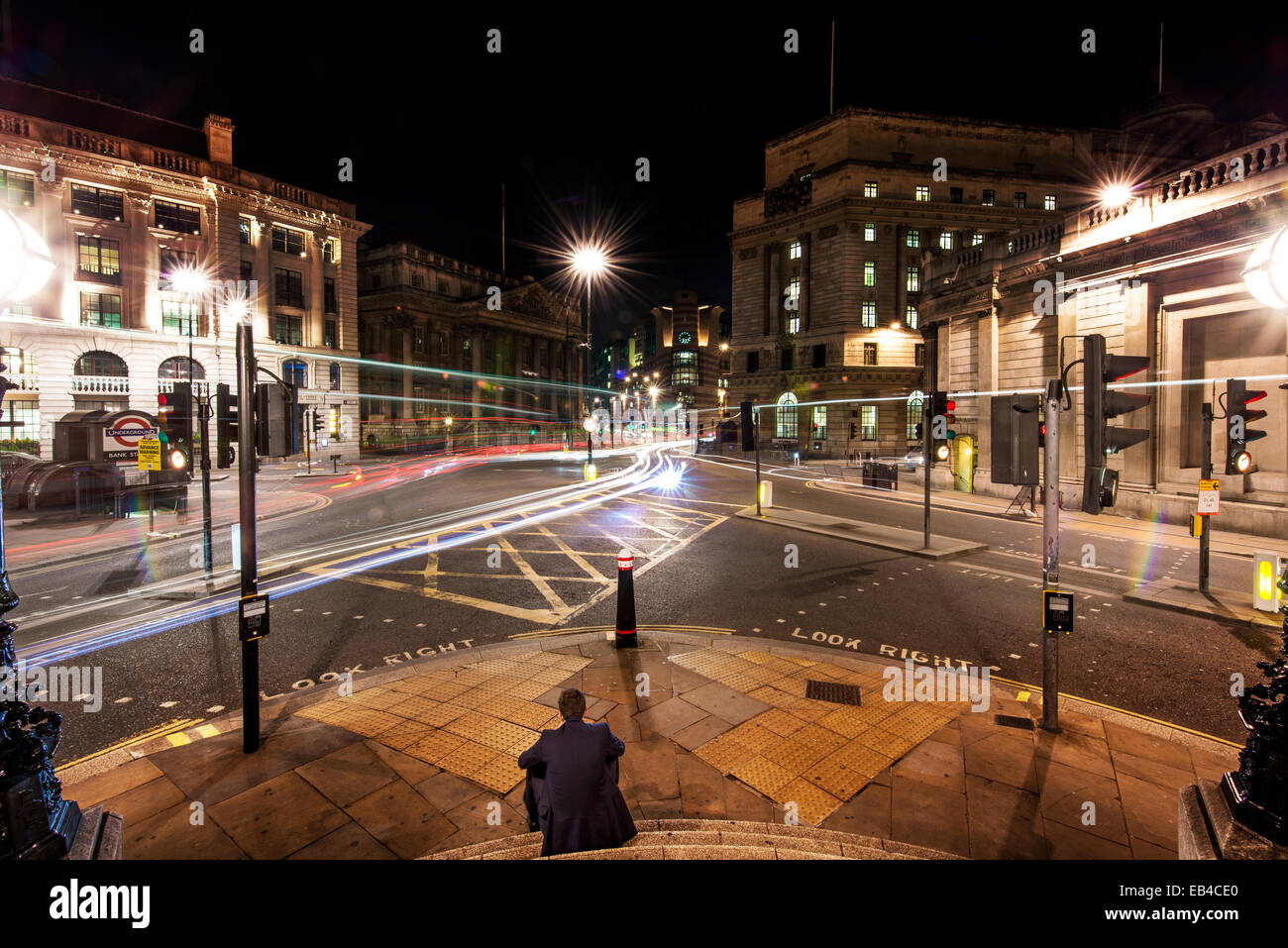 A single City worker sits on the steps of Bank Junction, City of London after midnight as cars drive by - Stock Image