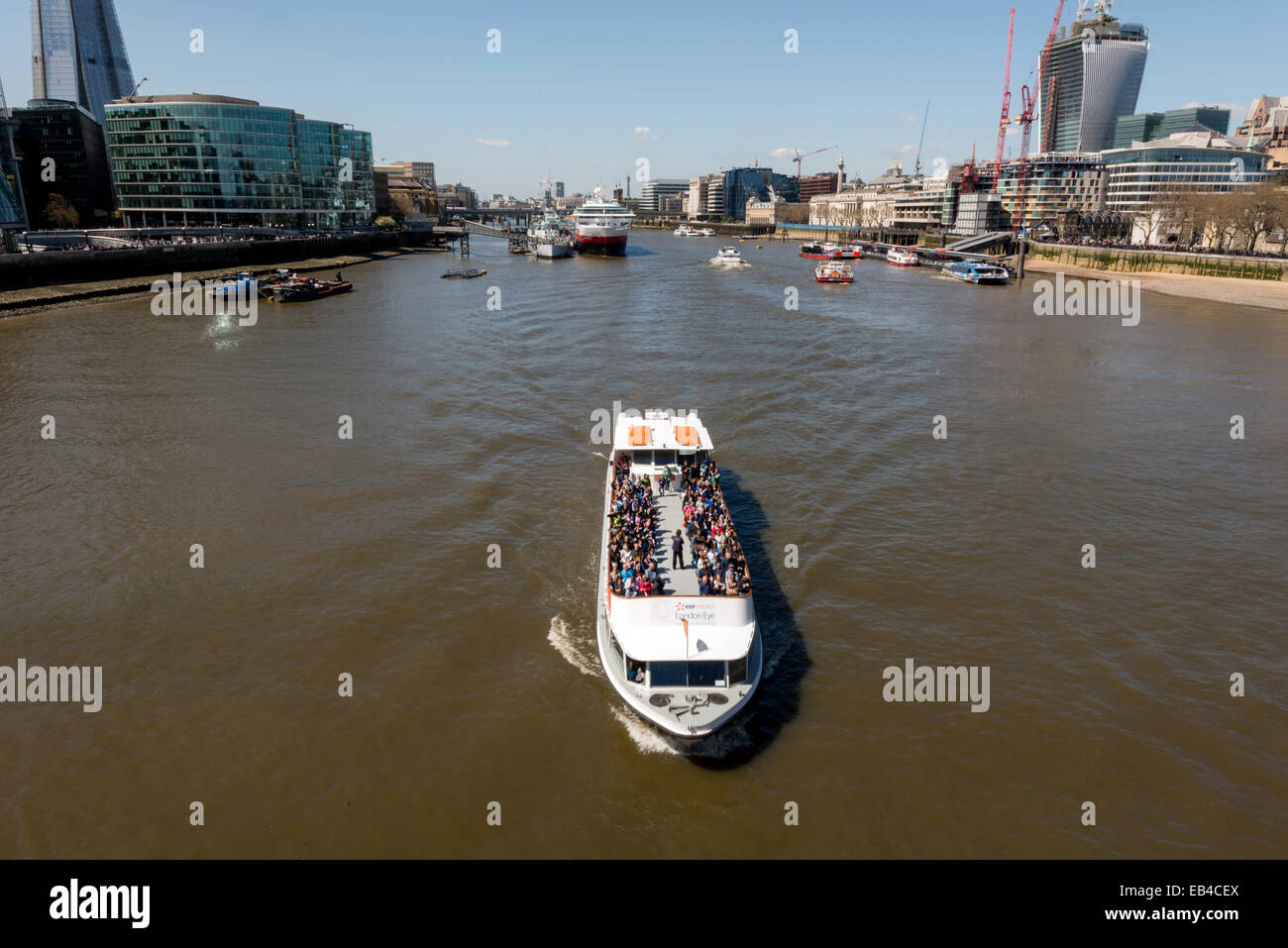 River Thames cruise boat passing under Tower Bridge with The City and Southbank backdrop - Stock Image