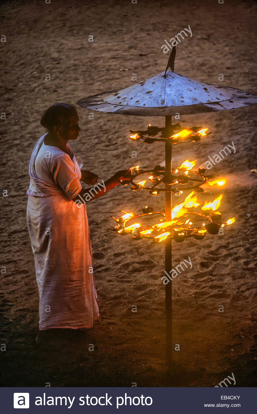 A Buddhist woman lights a coconut oil lamp near the sacred Bo Tree in Anuradhapura. - Stock Image