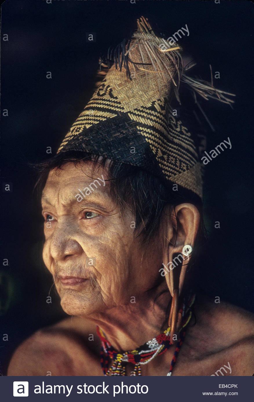 A Penan elder with a woven hat and an ear deformed by wearing heavy earrings,. - Stock Image
