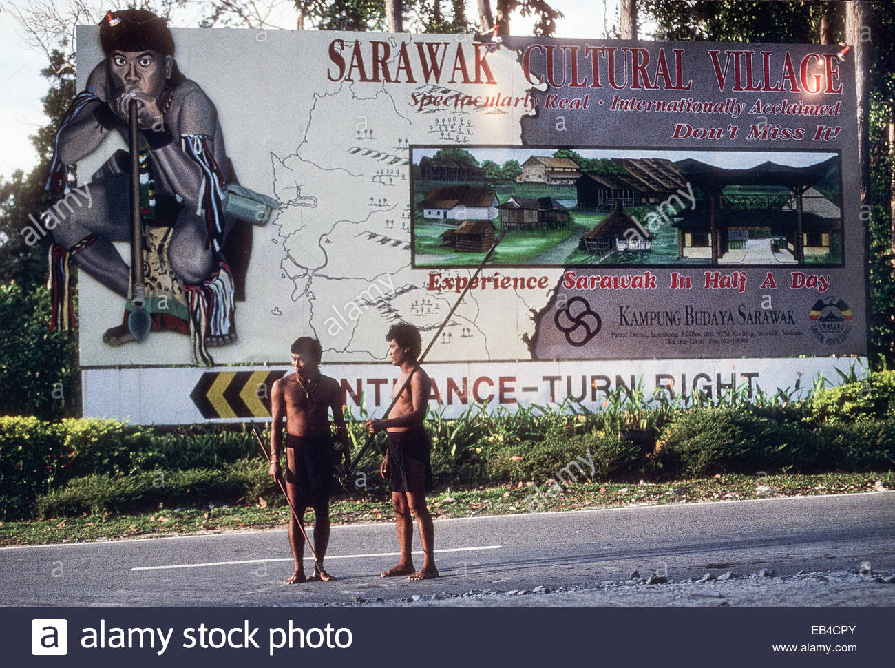 In a theme park, non-Penan men hired to represent the Penan, whose habitat is being destroyed. - Stock Image