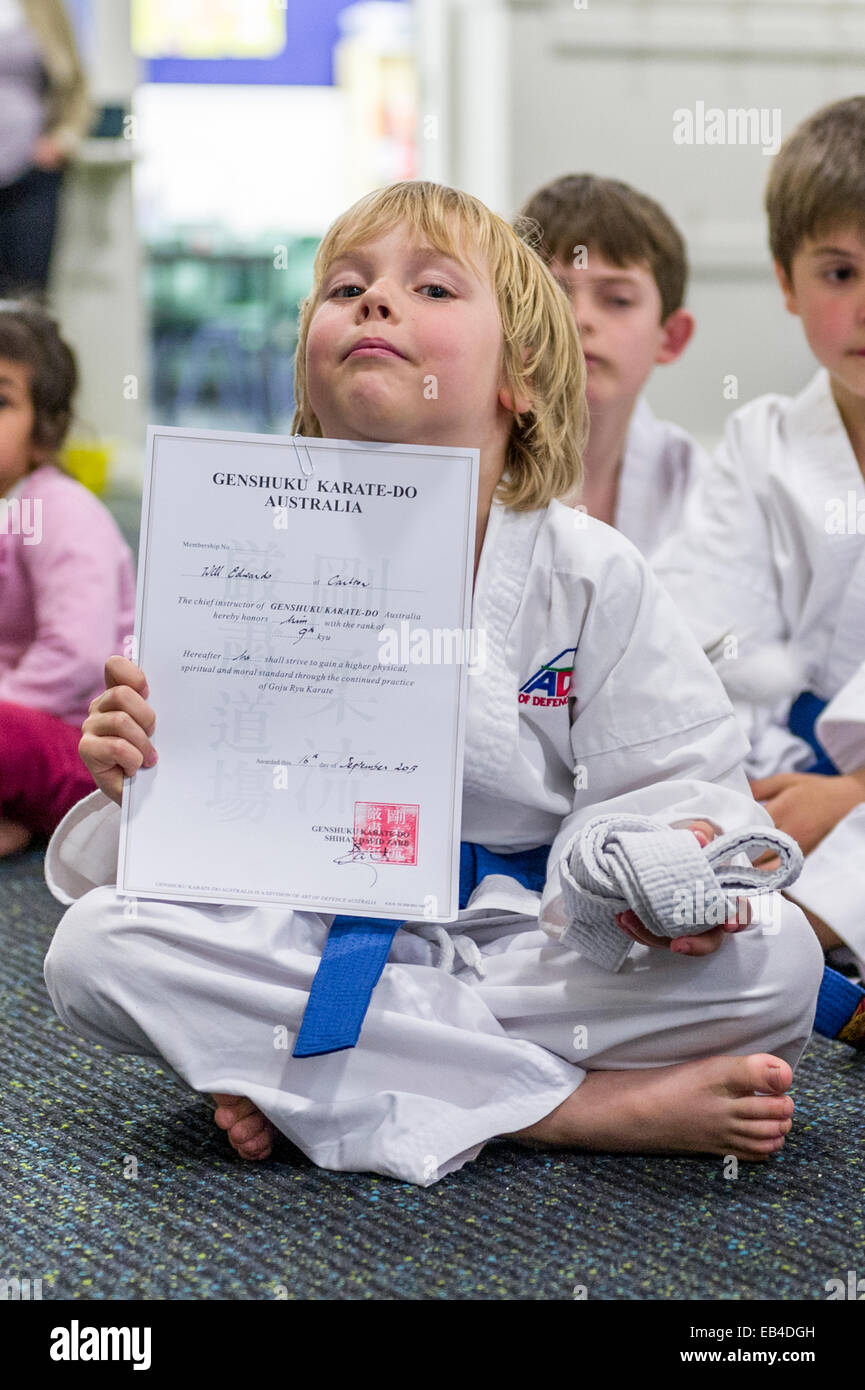 A boy displays his karate certificate awarded when he earned his blue belt. - Stock Image