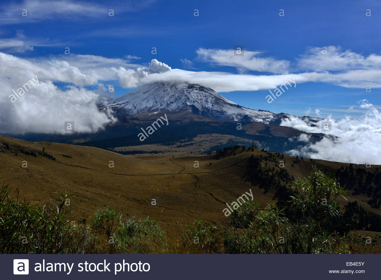 Clouds partially encircle smoking Popocatepetl Volcano. - Stock Image
