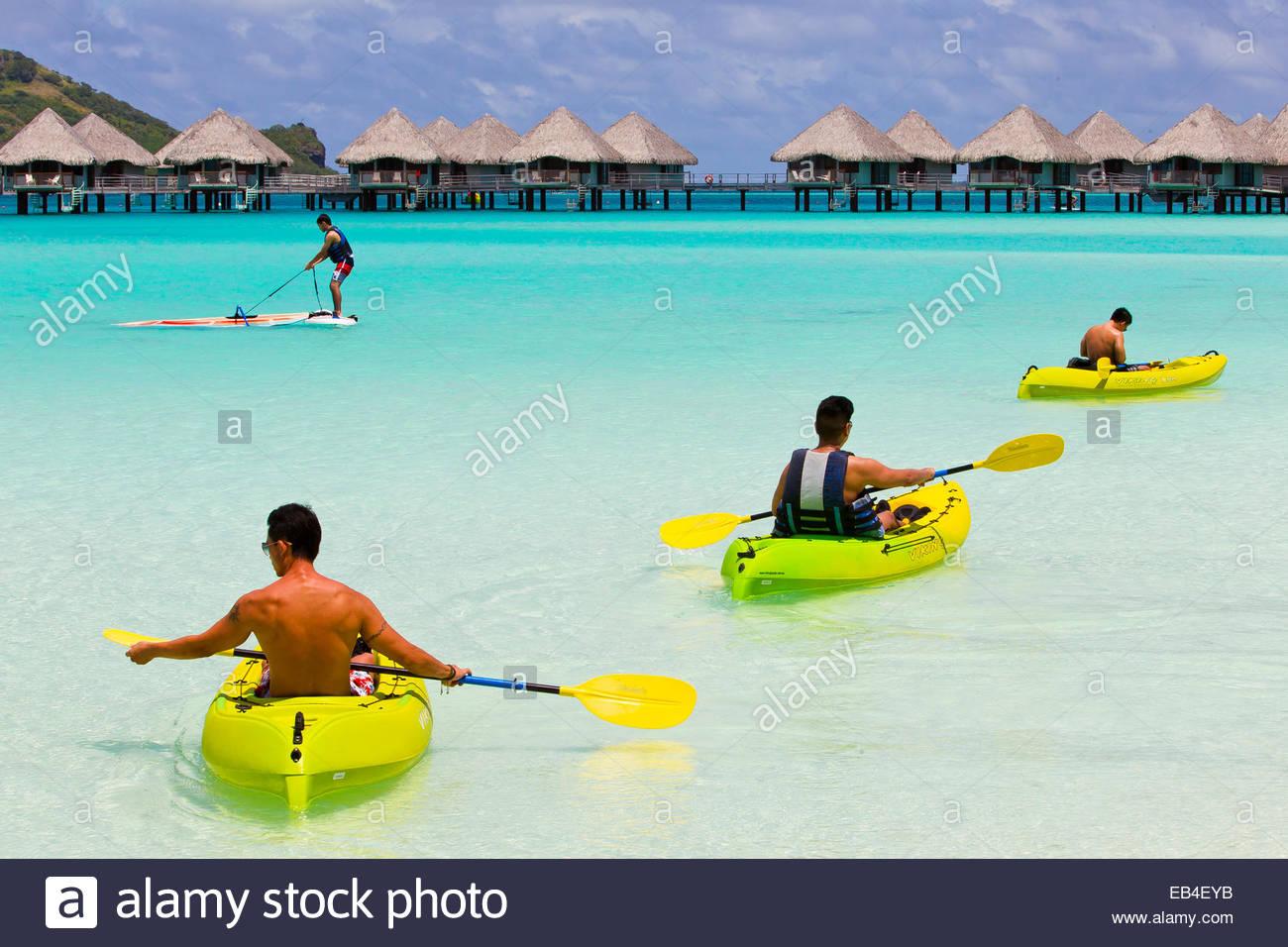 Tourists kayaking and wind surfing off the coast of Bora Bora. - Stock Image