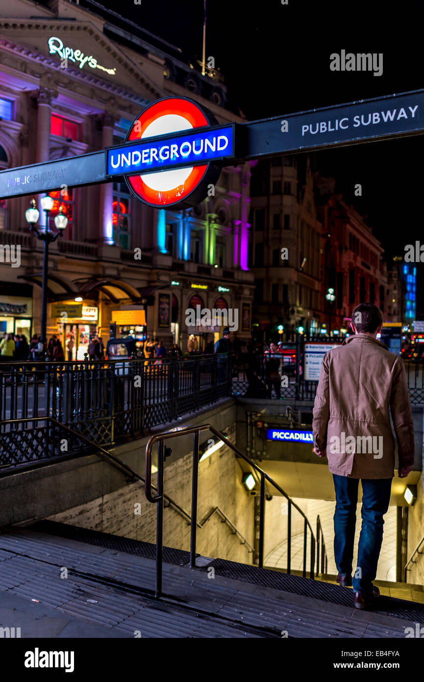 Last tube home: a man walks into Piccadilly Tube station to catch the last train home - Stock Image