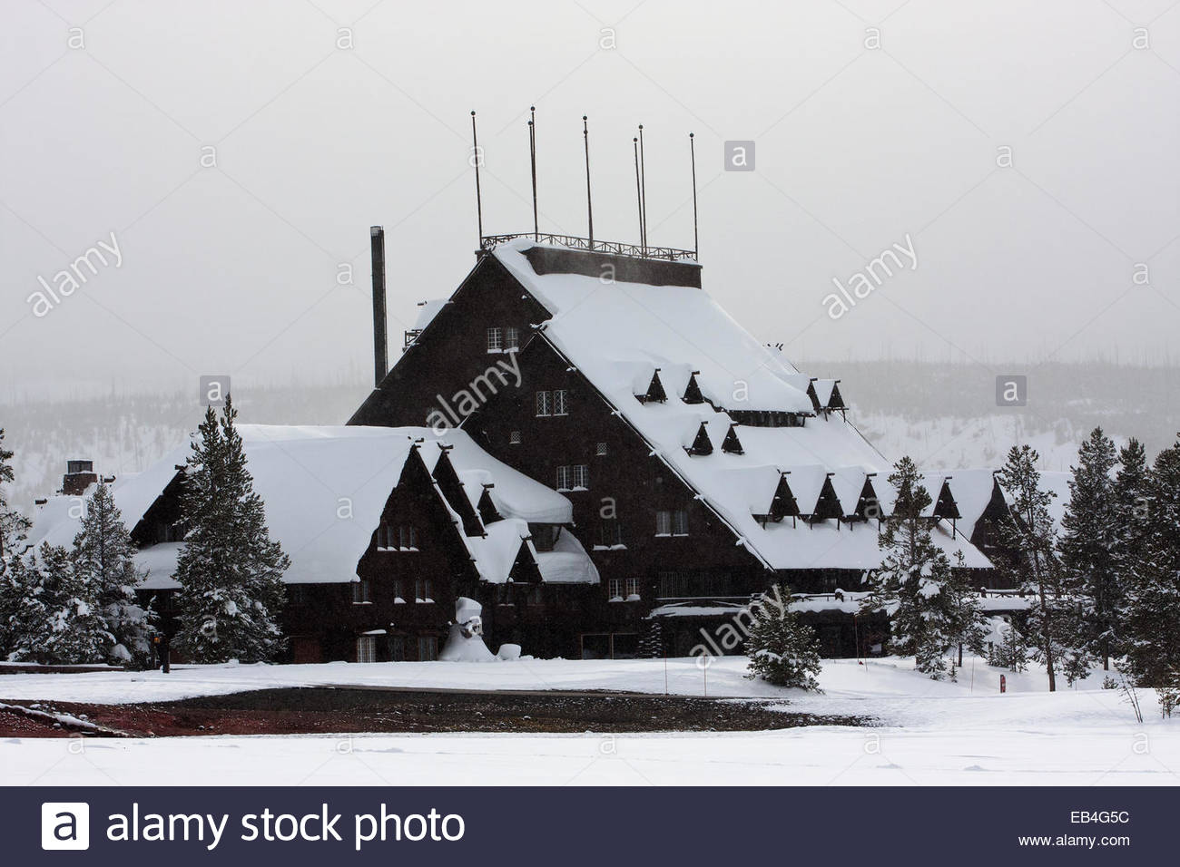 A scenic view of the historic Old Faithful Inn, in a snowy landscape. - Stock Image