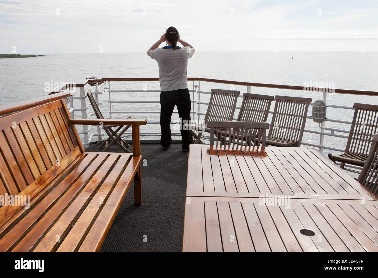 A passenger on an expedition vessel looks out at the Pacific Ocean en route to the Galapagos Islands. - Stock Image