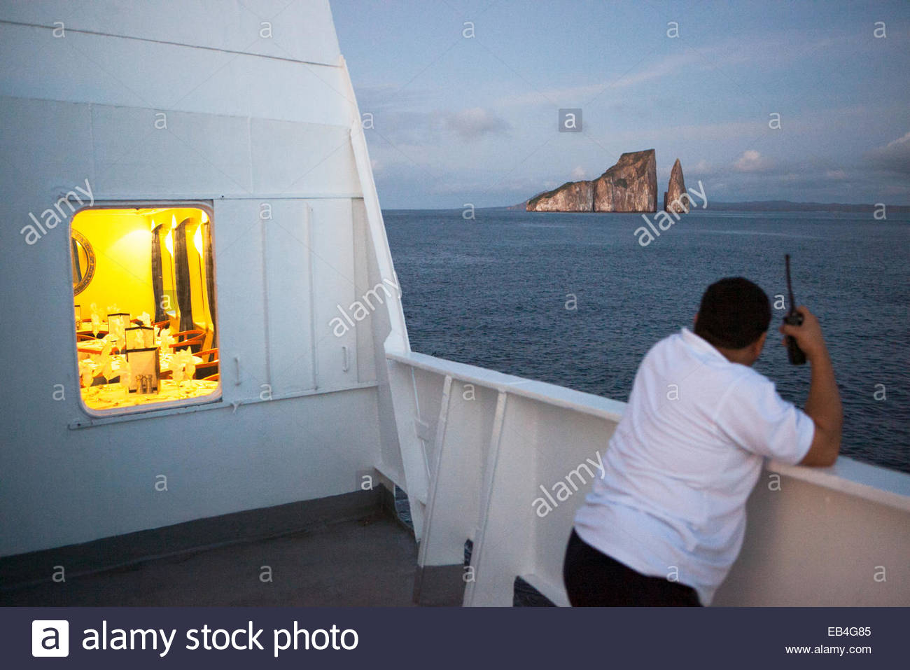 A staff member aboard a tourism expedition vessel looks out at rock formations en route to the Galapagos Islands. Stock Photo