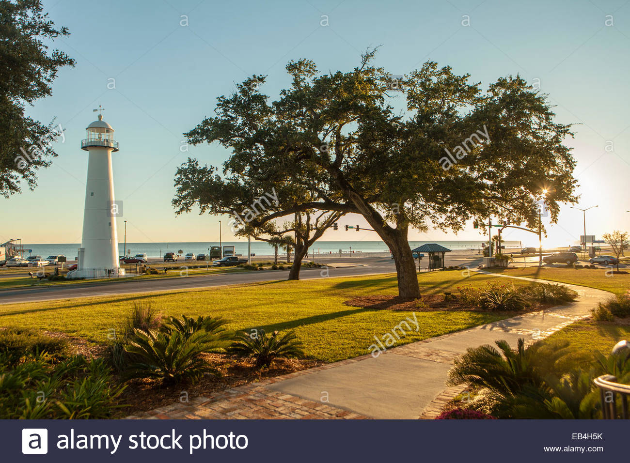 A path curves toward the historic Biloxi Light on the Gulf of Mexico during the afternoon golden hour. - Stock Image
