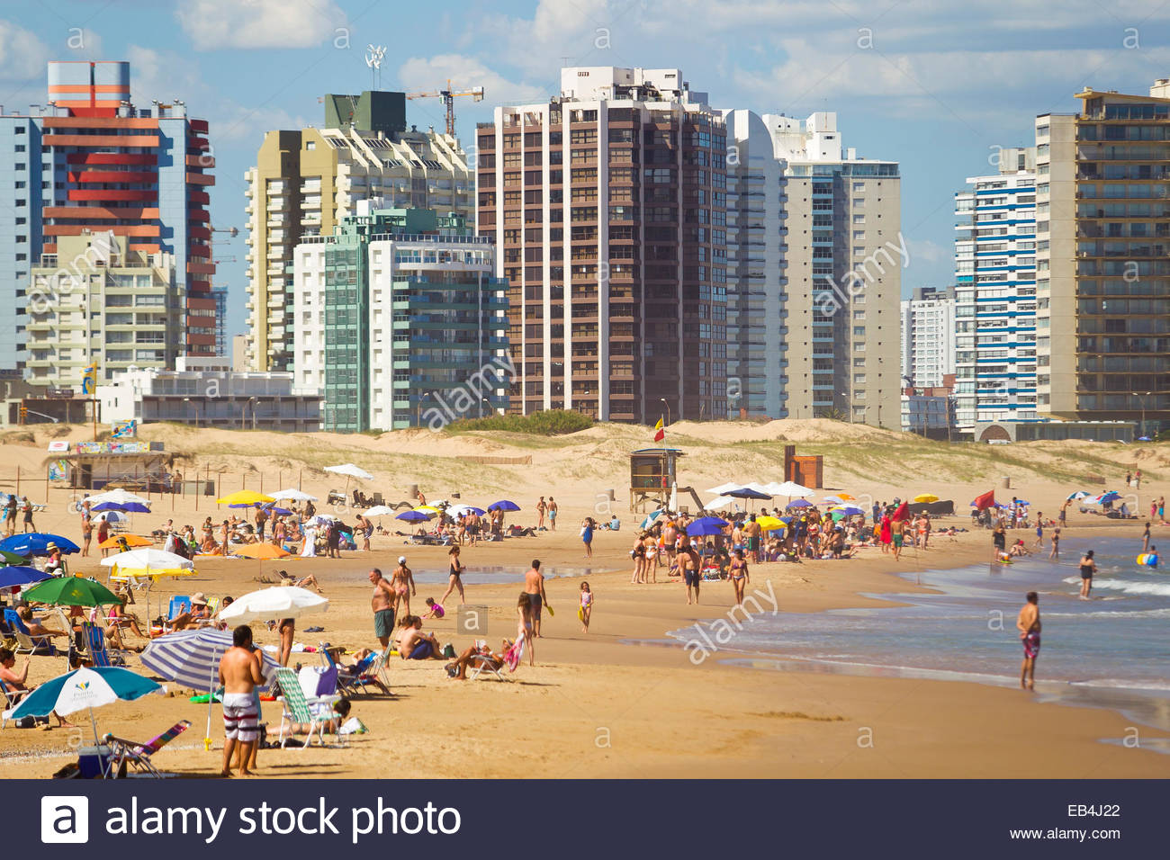 Sunbathers and swimmers enjoying a hot day on a city beach on the Atlantic coast. - Stock Image