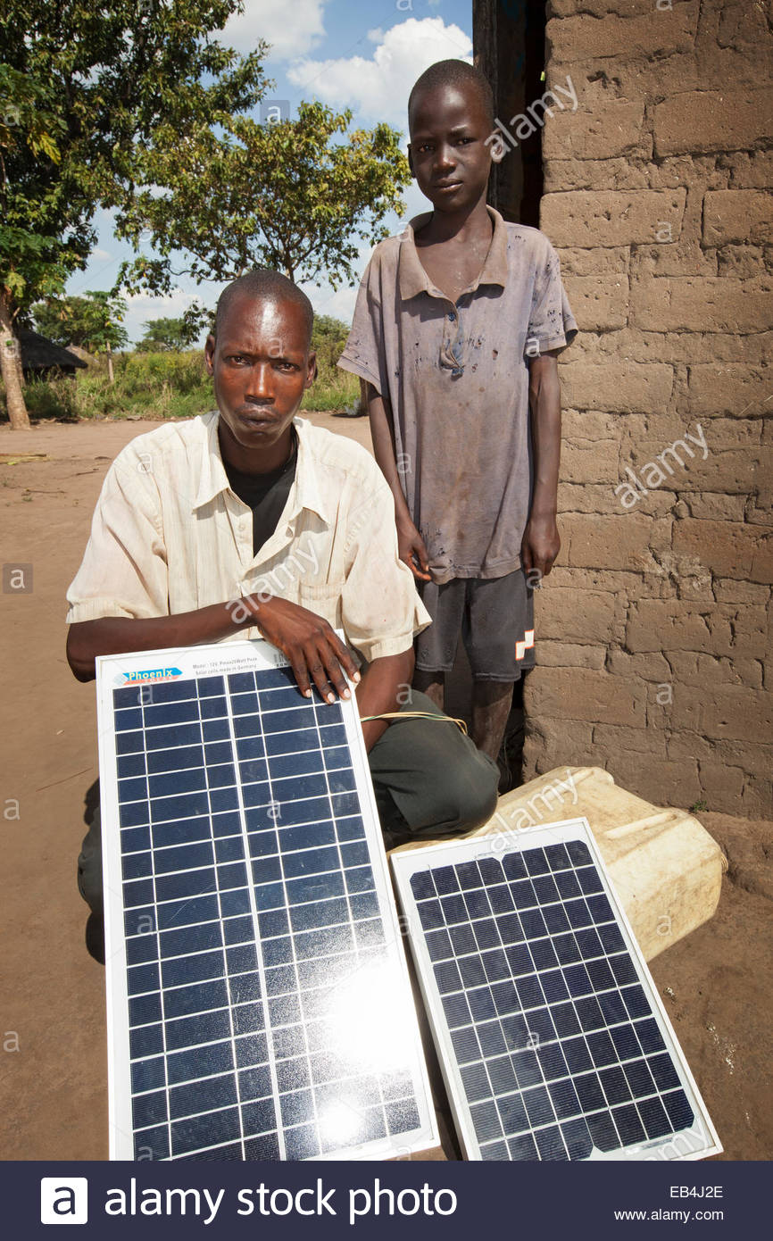 A business owner poses with his son and the solar panels that power his shop. - Stock Image