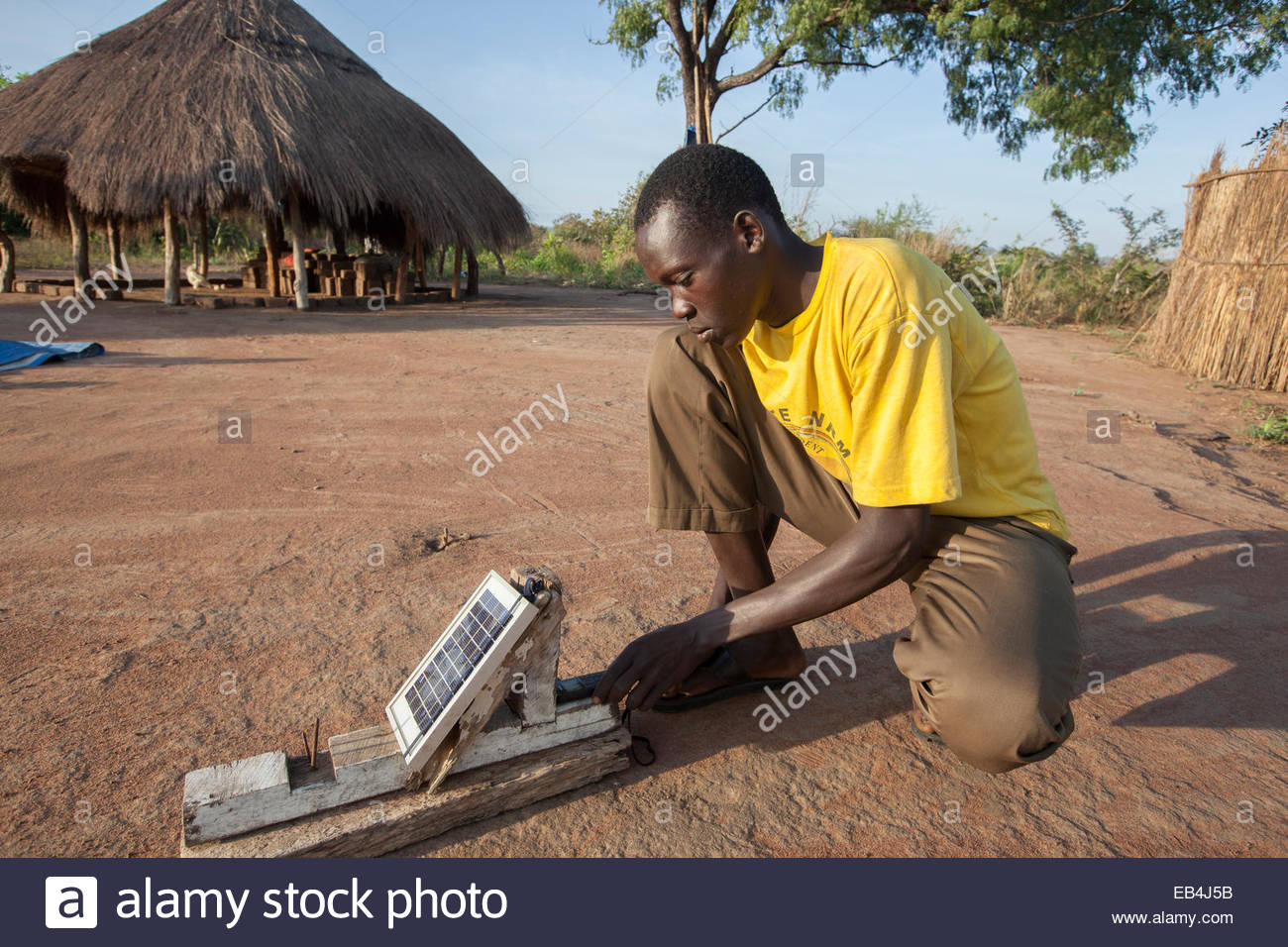 A young man uses a solar charger to power his mobile device. Stock Photo