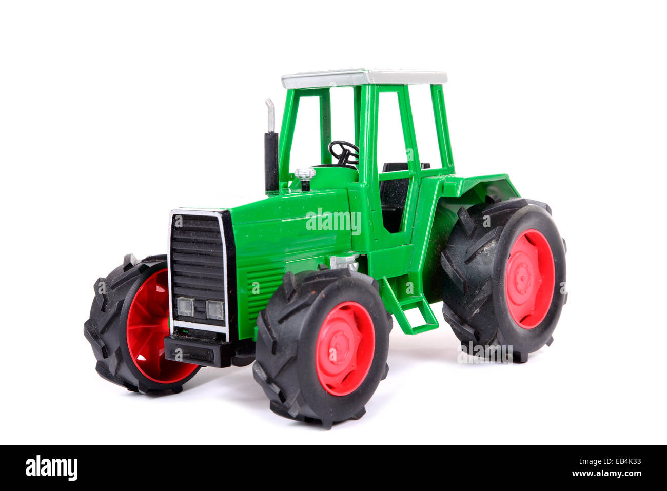 green toy farm tractor on the white background - Stock Image