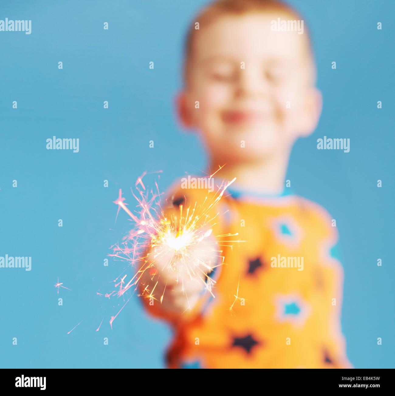 Blurred portrait of child holding a sparkler - Stock Image
