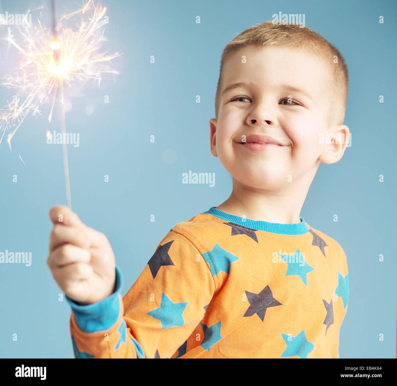 Delighted kid watching a sparkler - Stock Image