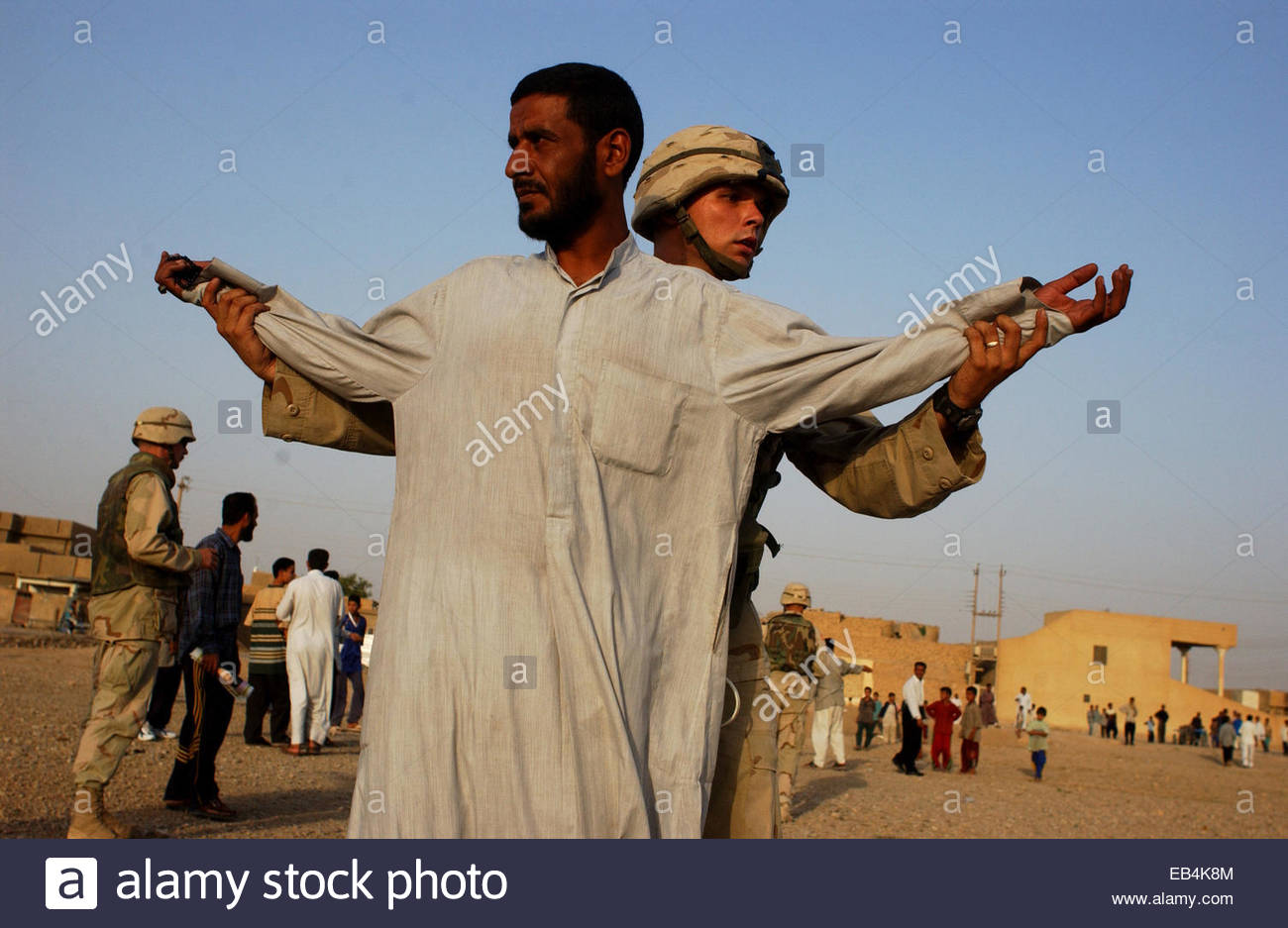A soldier frisks an Iraqi man as the latter leaves a suspected outdoor weapons market in Narahwan on the outskirts - Stock Image