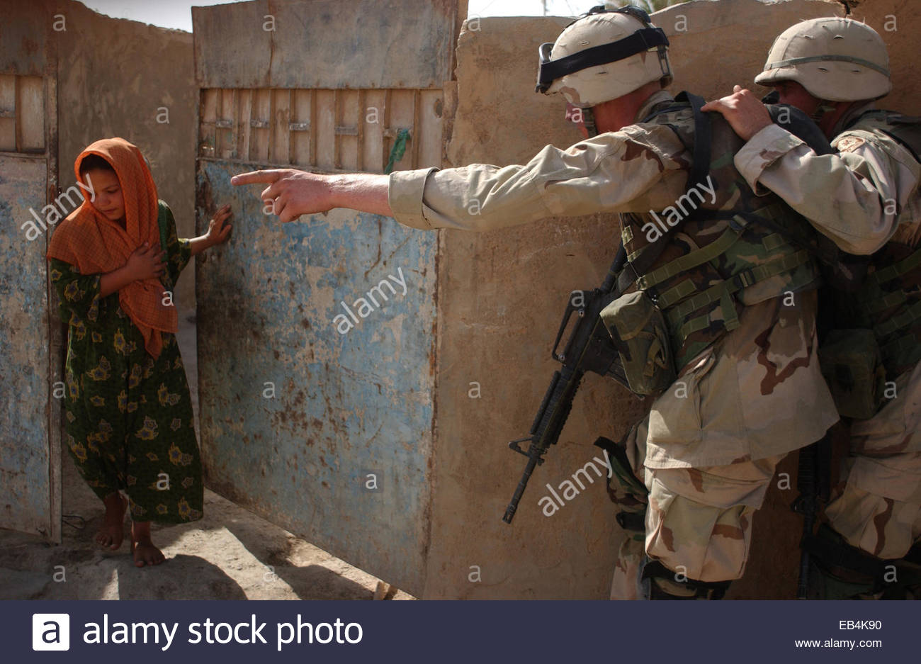 Soldiers from the 1st Squadron, 2nd Armored Cavalry Regiment order an Iraqi girl from her home before they enter - Stock Image