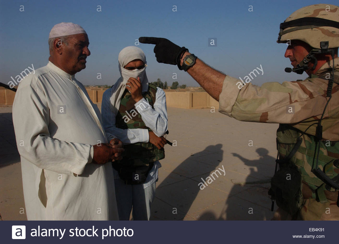A Staff Sergeant of the 1st Squadron, 2nd Armored Cavalry Regiment talks to an Iraqi in whose home soldiers found - Stock Image