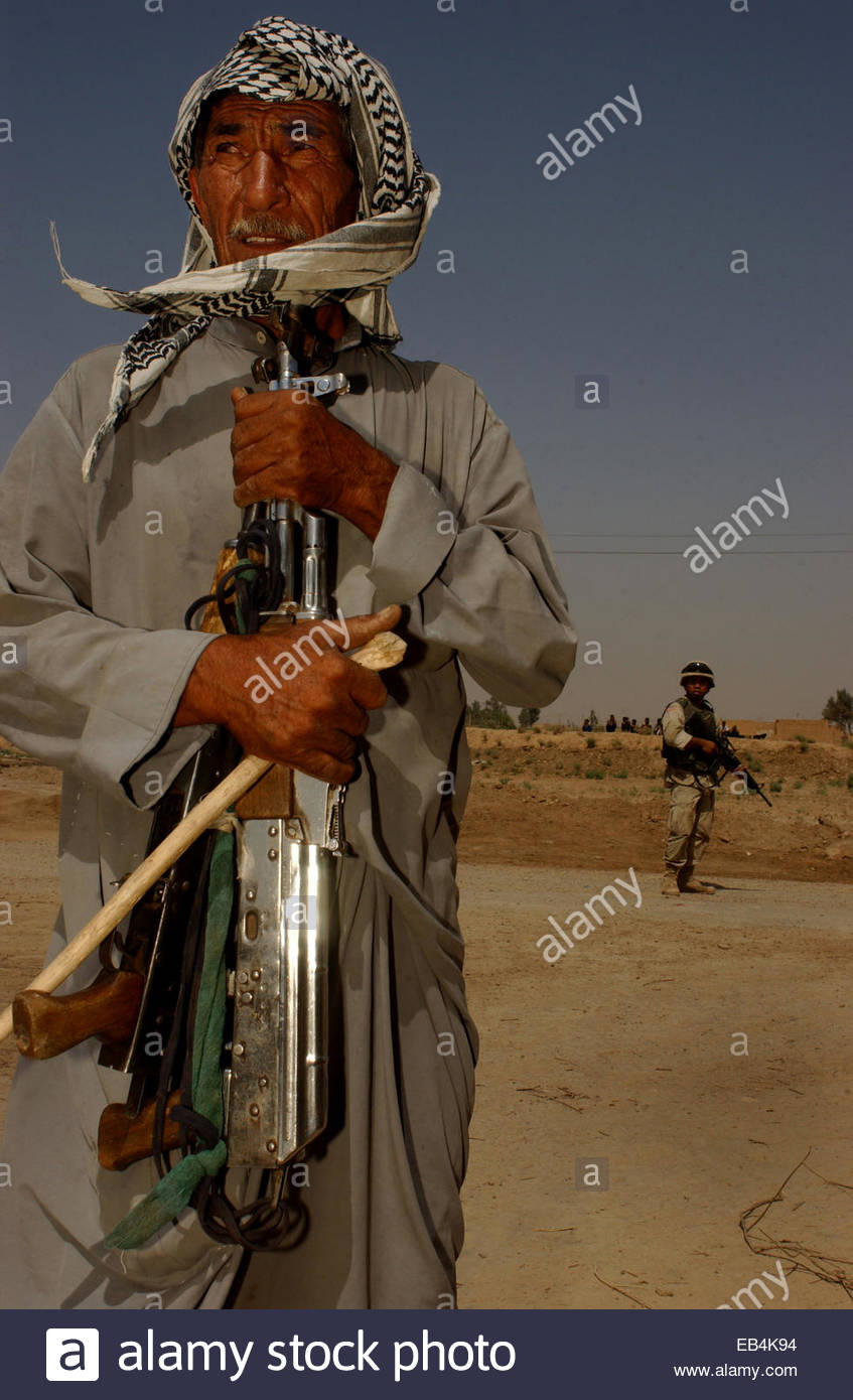 An Iraqi holds his two AK-47 rifles that were returned by the US military after a raid on the industrial compound - Stock Image