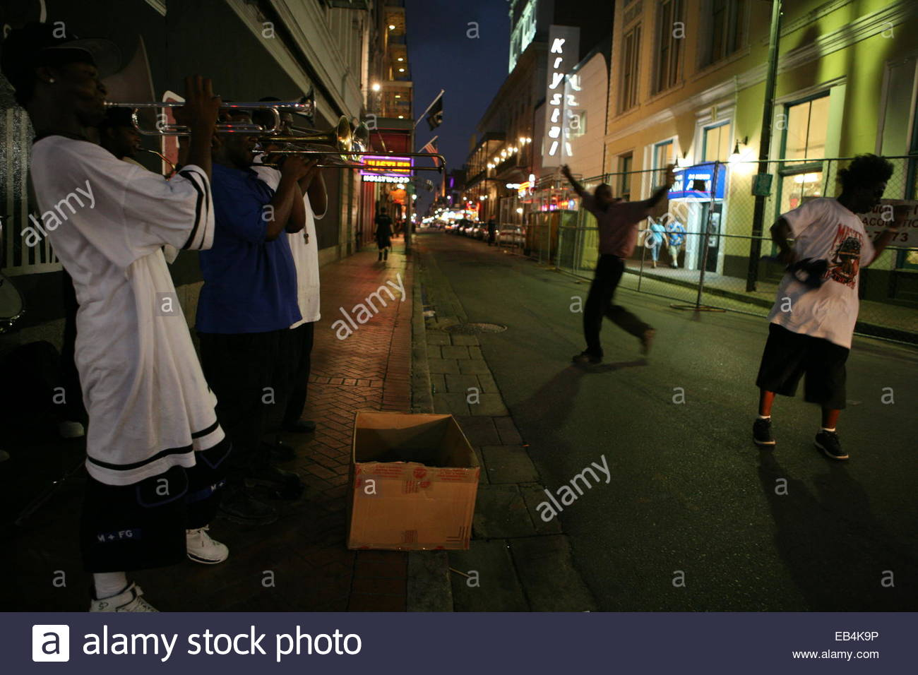 Dancing to music played on a street corner in the French Quarter of New Orleans. - Stock Image