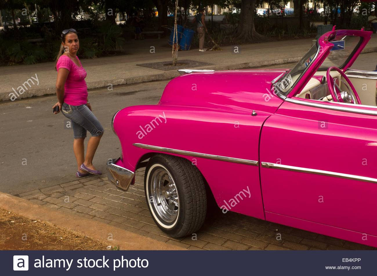 A woman in a pink T shirt walks past a hot pink vintage American car. Stock Photo