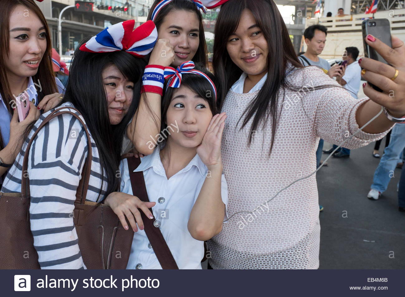 Young female anti-government demonstrators taking a group self portrait. - Stock Image
