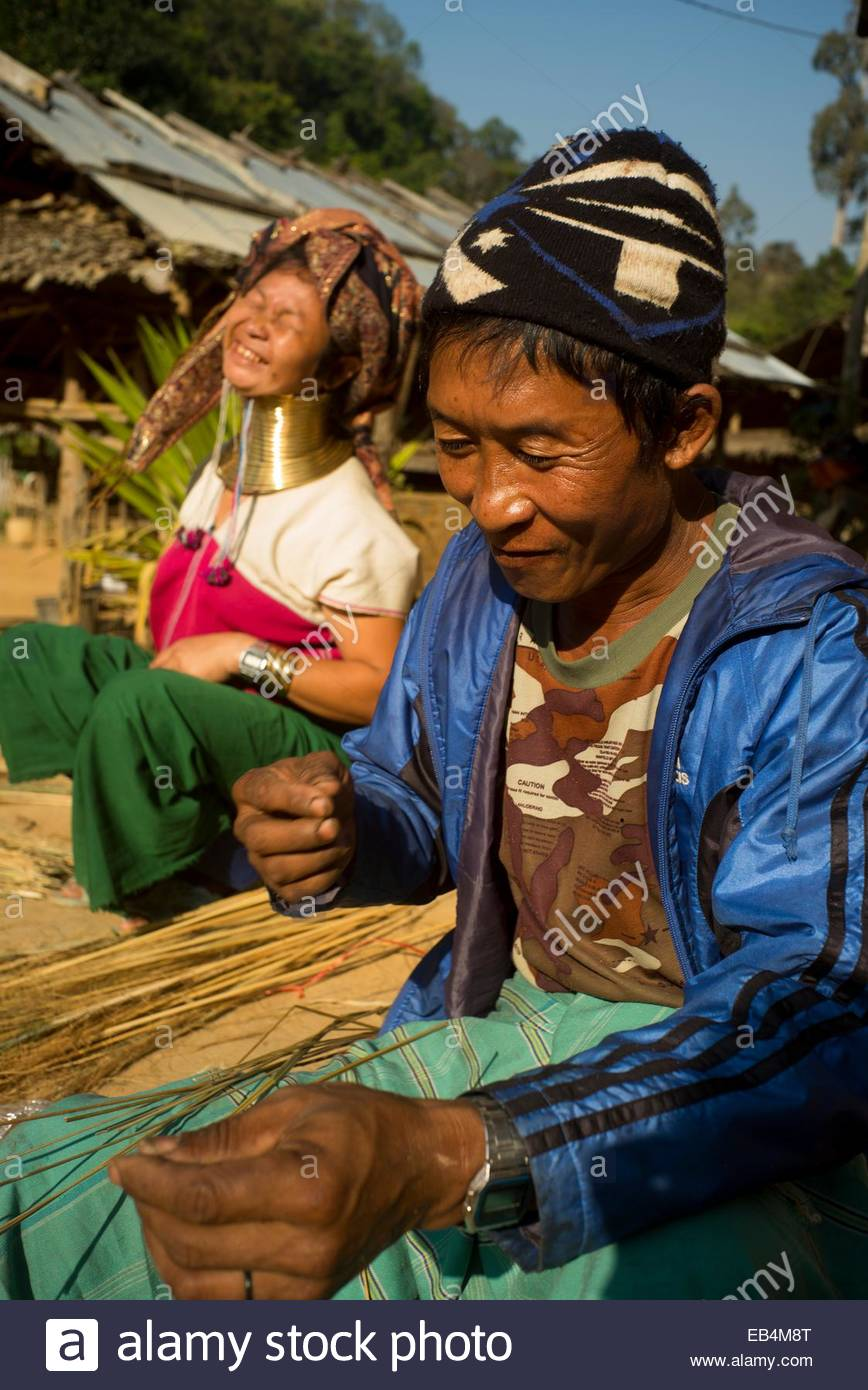 A Shaman interprets bamboo stalks for a long neck woman in a Karen village. - Stock Image