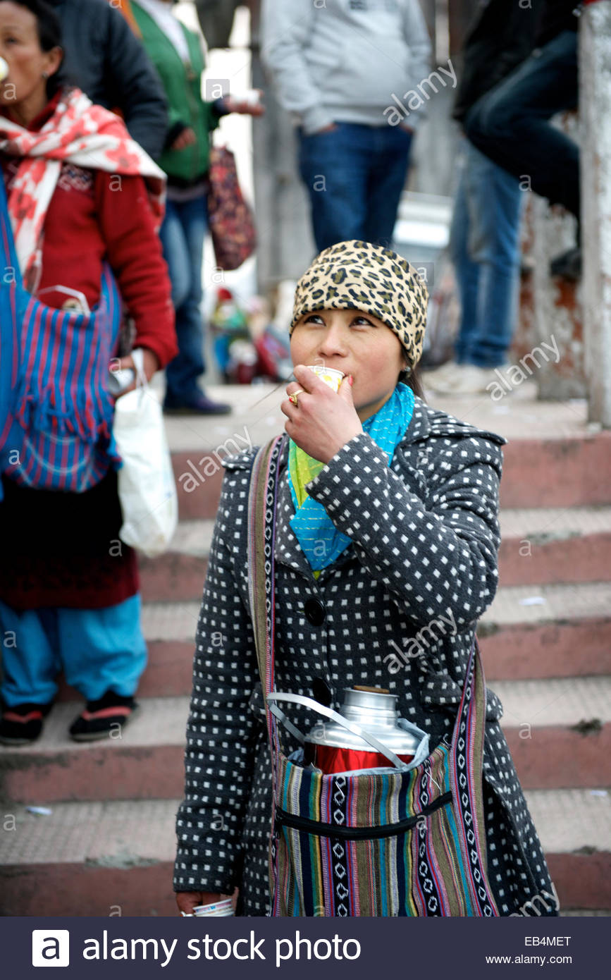 A tea seller fortifies herself with a sip of her own brew. - Stock Image