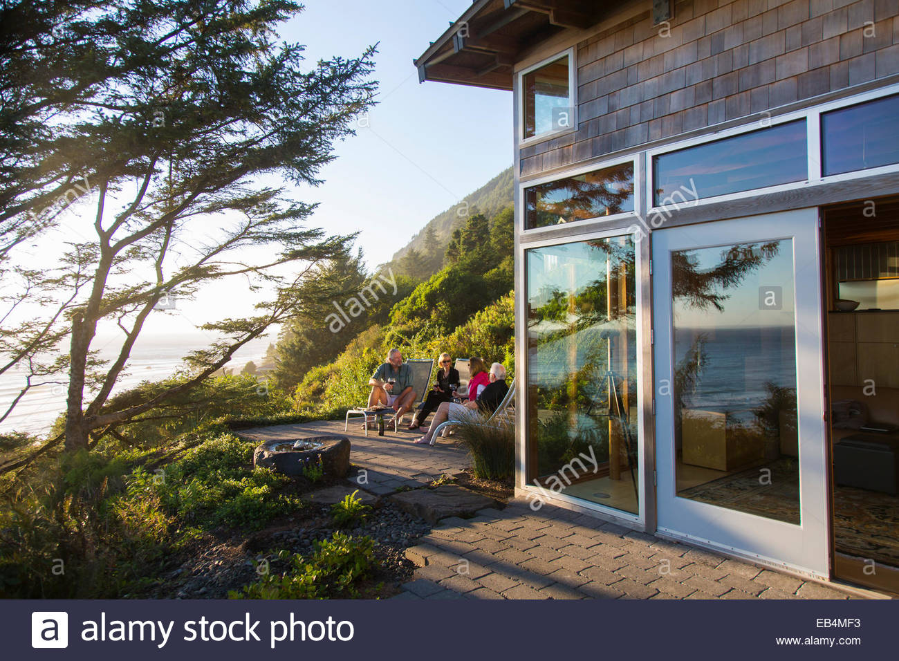 A couple entertain their guests on a patio of their B & B overlooking the Pacific ocean. - Stock Image