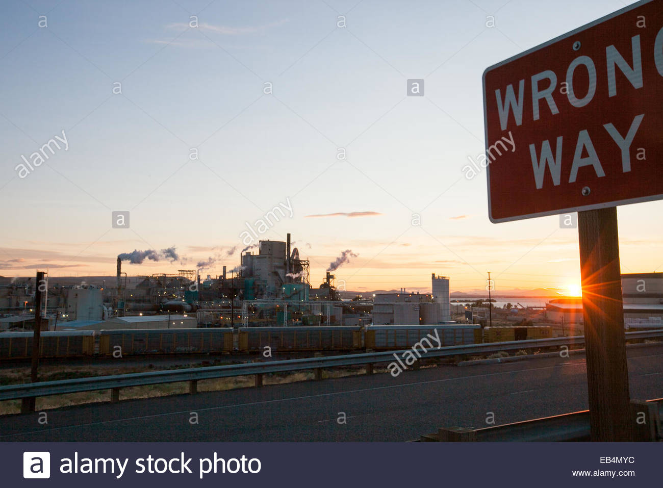 A Wrong Way sign on a road near a paper manufacturing and packing plant. - Stock Image