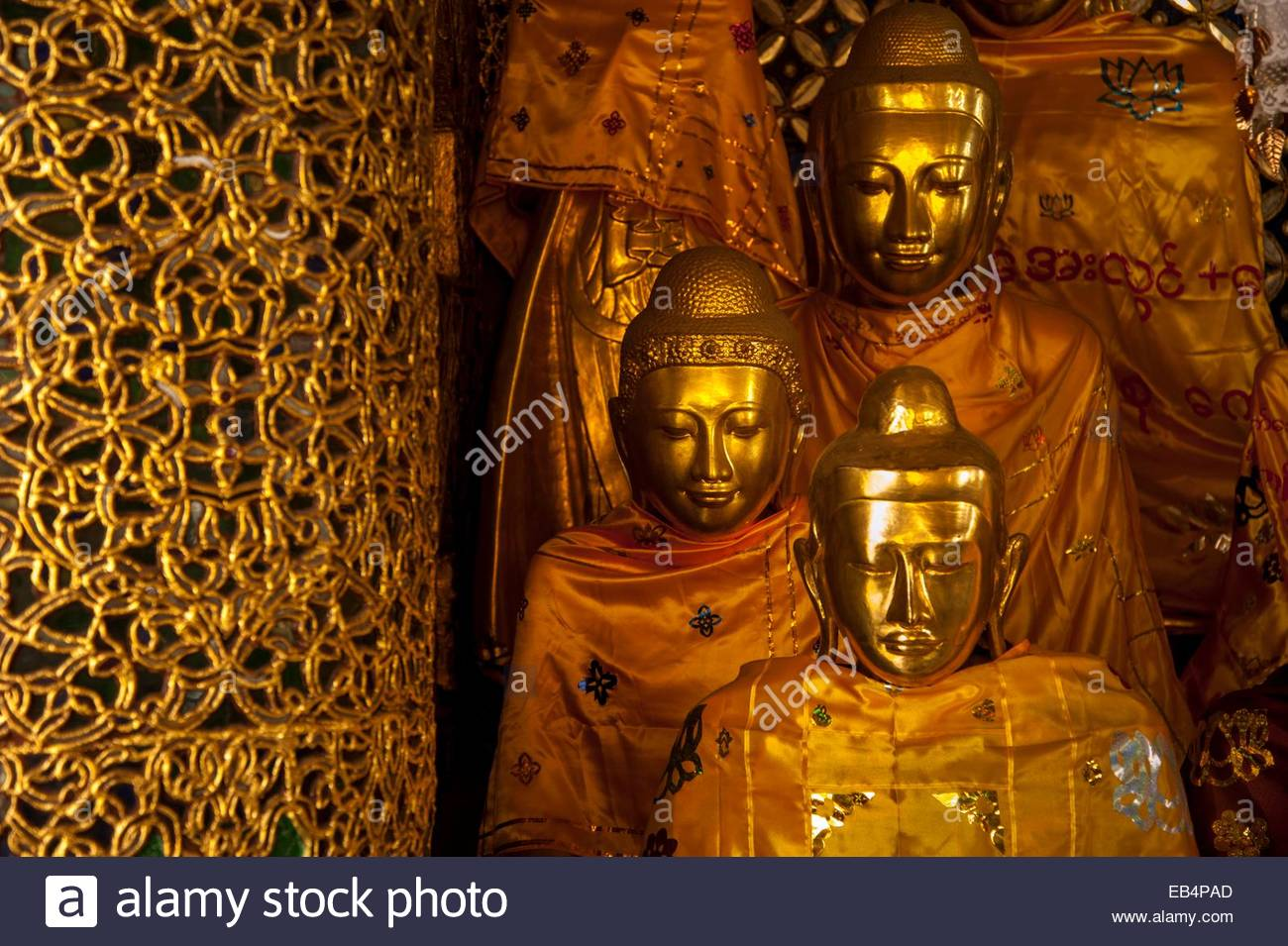 Statues of Buddha draped in saffron robes. - Stock Image