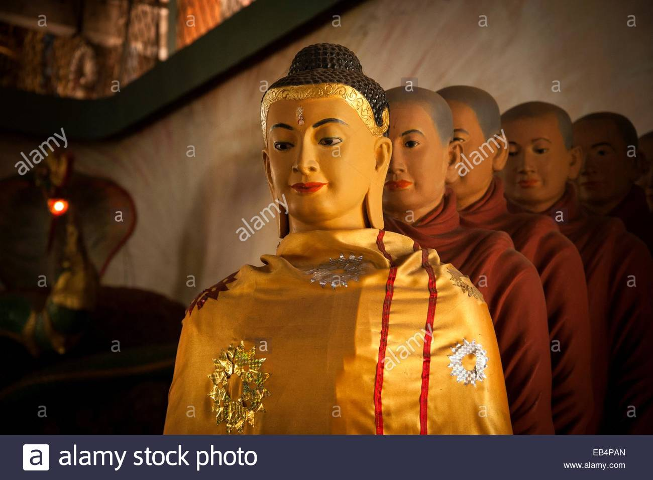 Statues of Buddha draped in saffron robes at the Ngadatkyi Pagoda. - Stock Image