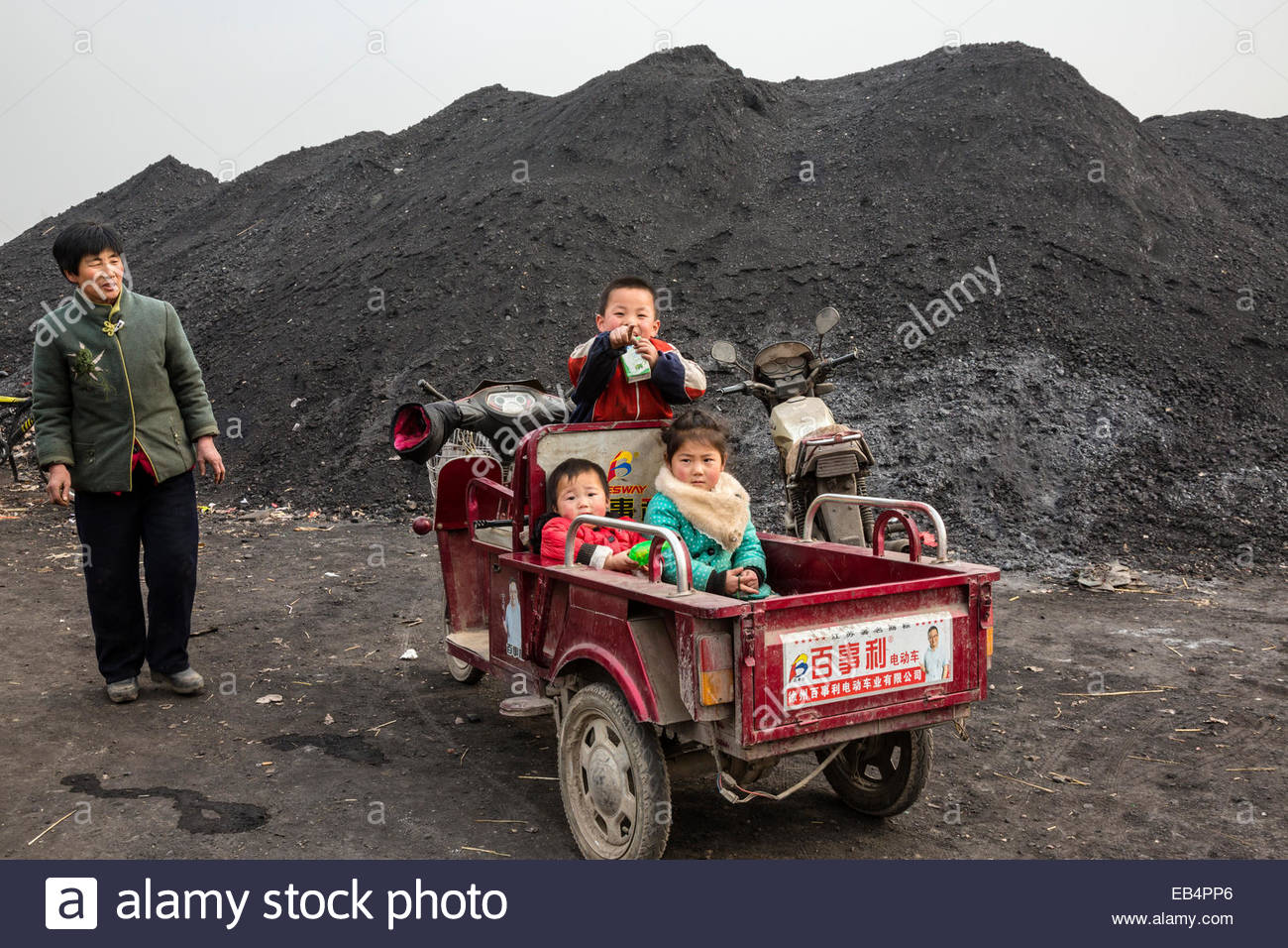 Children in a motorized vehicle wait at a coal depot for their mother. - Stock Image