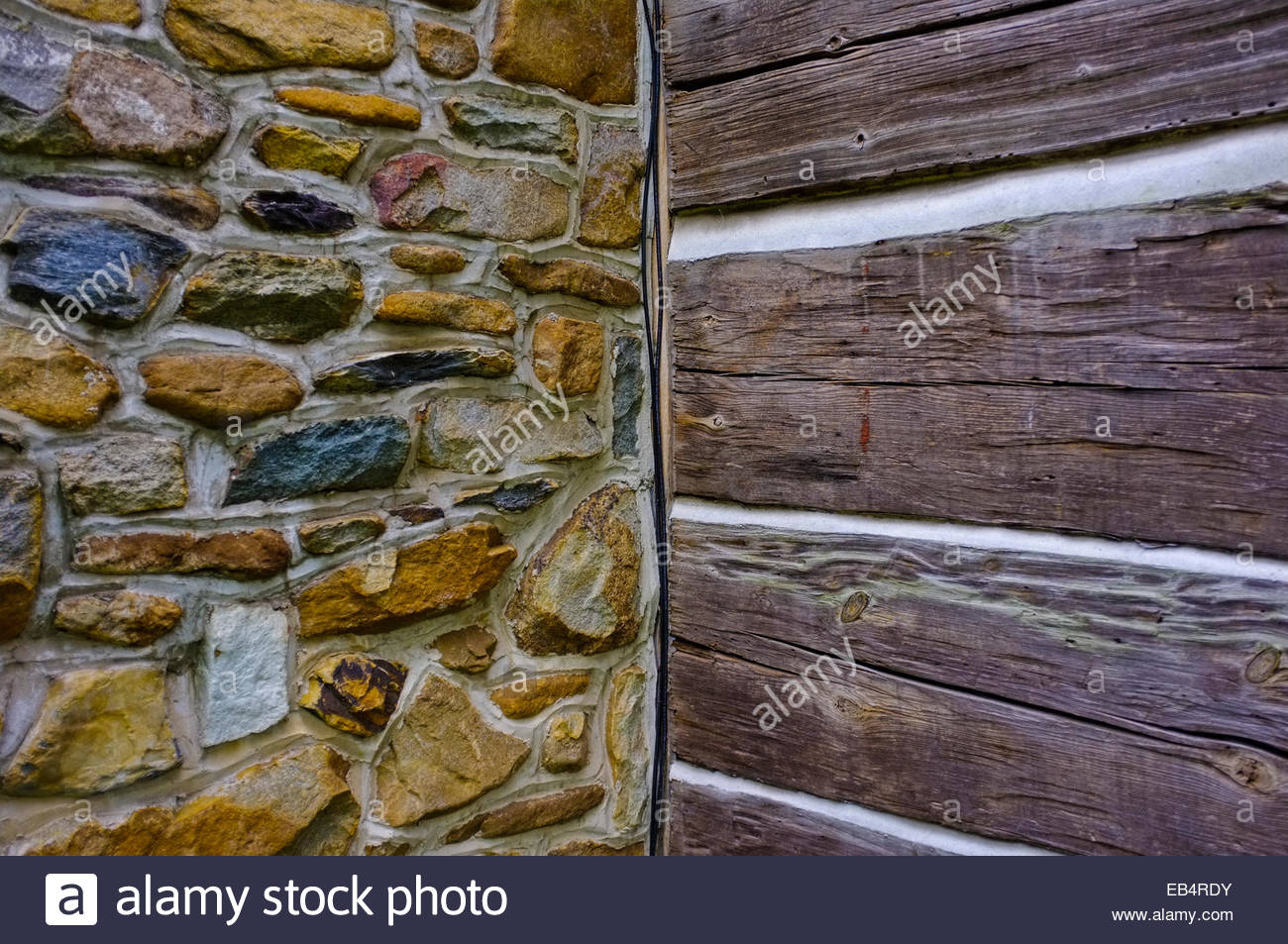 The corner of a log house where the logs meet the stone chimney. - Stock Image