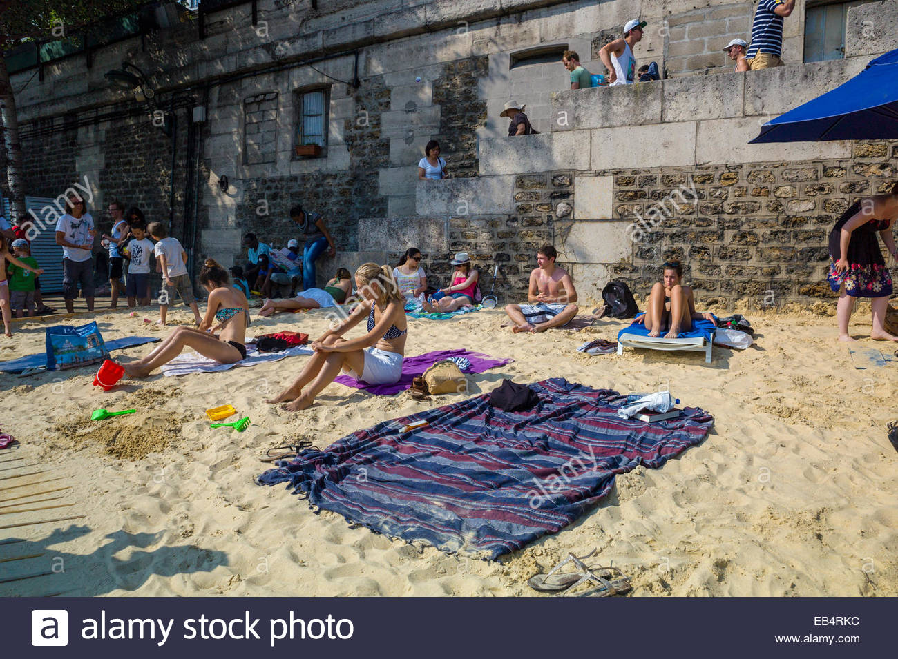 Parisians and tourists at Paris Plage, an artificial, temporary beach on the bank of the Seine River. Stock Photo