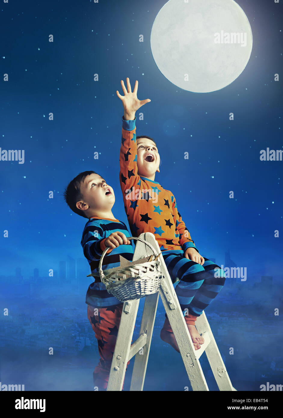 Two little brothers catching the huge moon - Stock Image