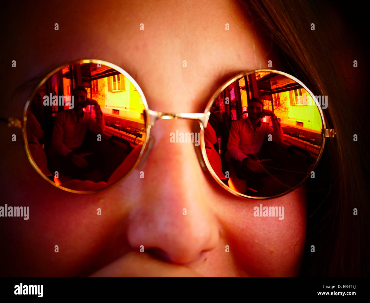 A young girl with reflective sunglasses - Stock Image