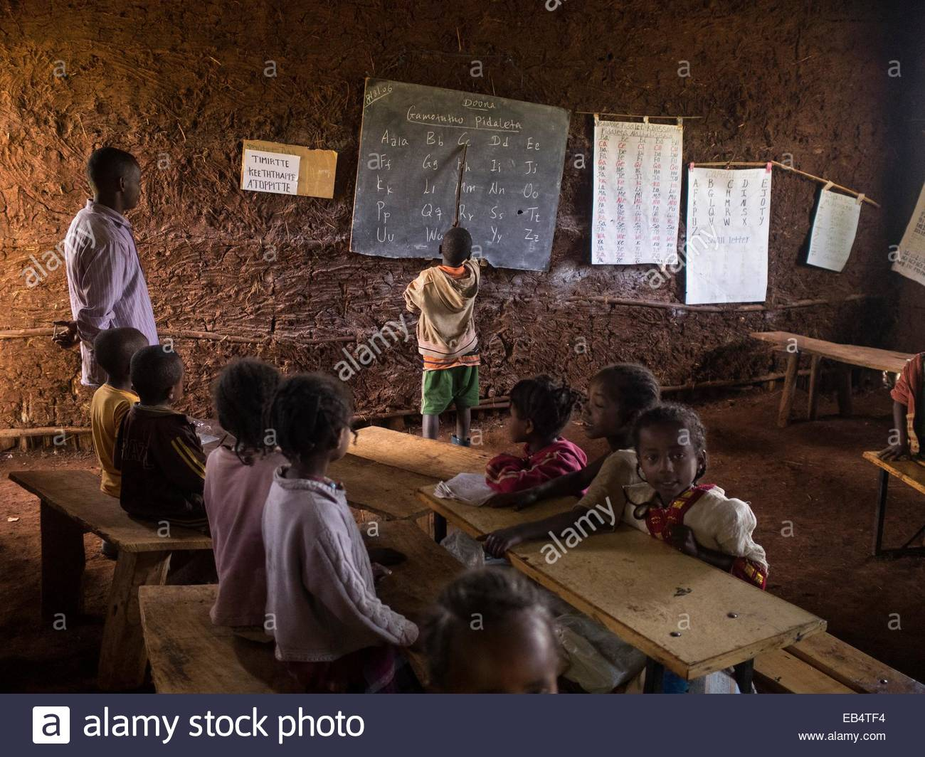 A boy points to Latin alphabet letters on a blackboard. - Stock Image